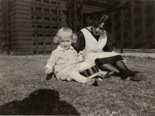 A very young, blond Jeff with nurse on the lawn at Hoover Street, circa 1921